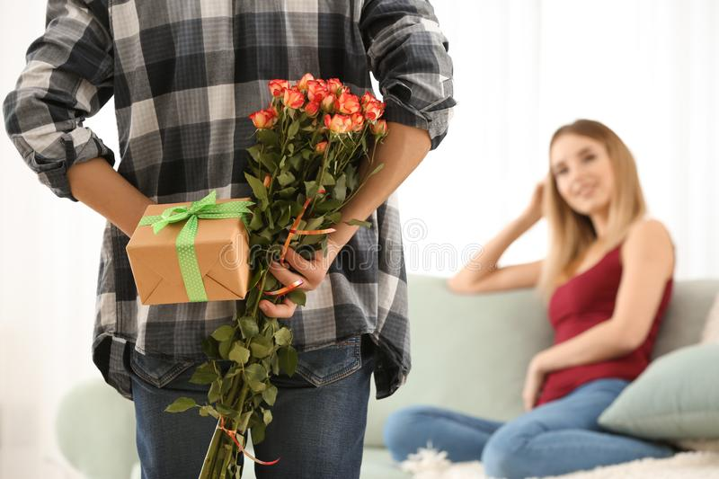 Young man hiding gift and flowers for girlfriend behind his back at home royalty free stock images
