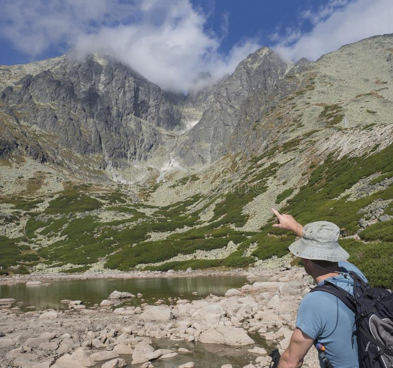 Young man hiker looking and point to mountain Peak Lomnicky stit 2 634 m at Summer, the highest mountain peaks in the stock photography
