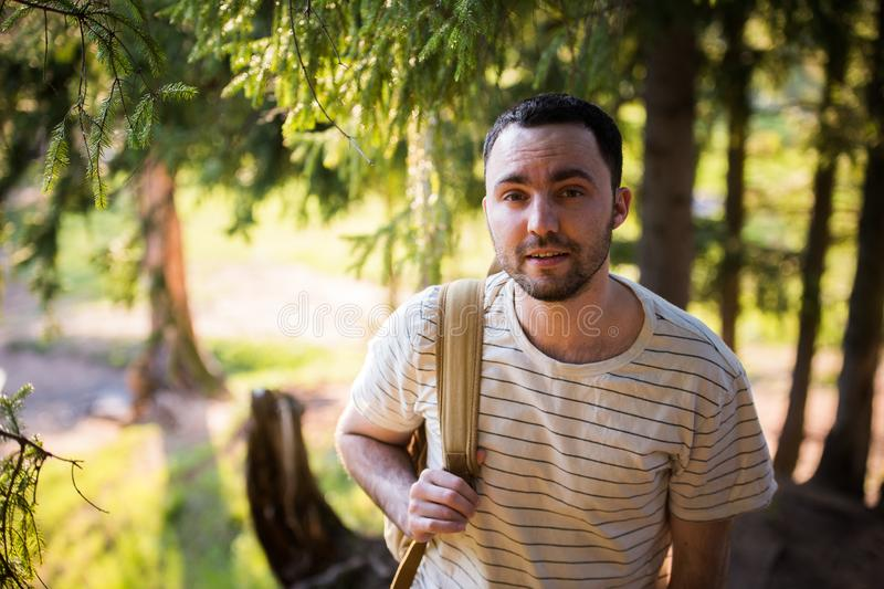 Young man hiking smiling happy portrait. Male hiker walking in forest stock photo