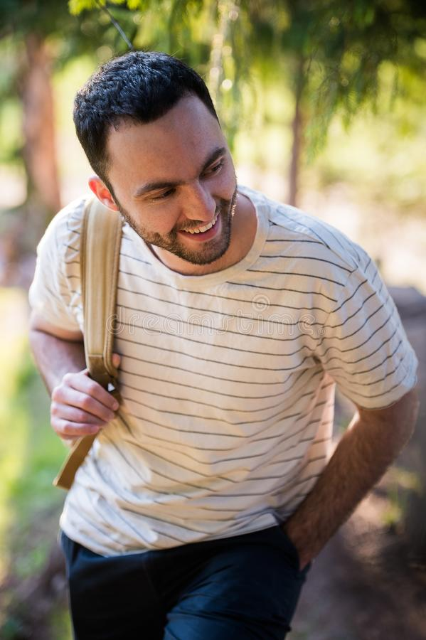 Young man hiking smiling happy portrait. Male hiker walking in forest royalty free stock photography