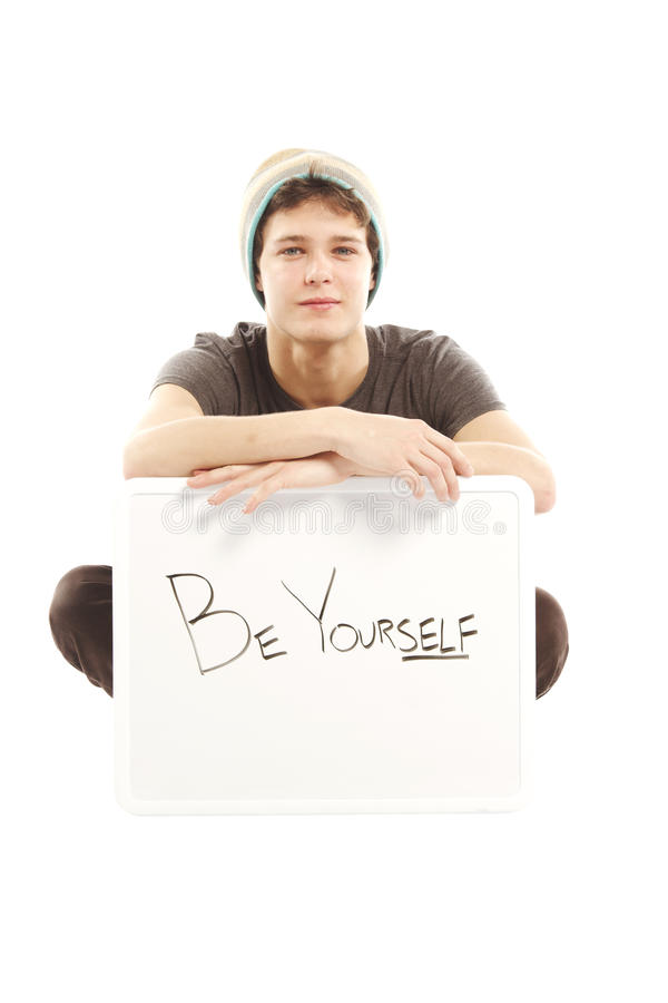 Young man with hip style holding sign. That says be yourself stock photography