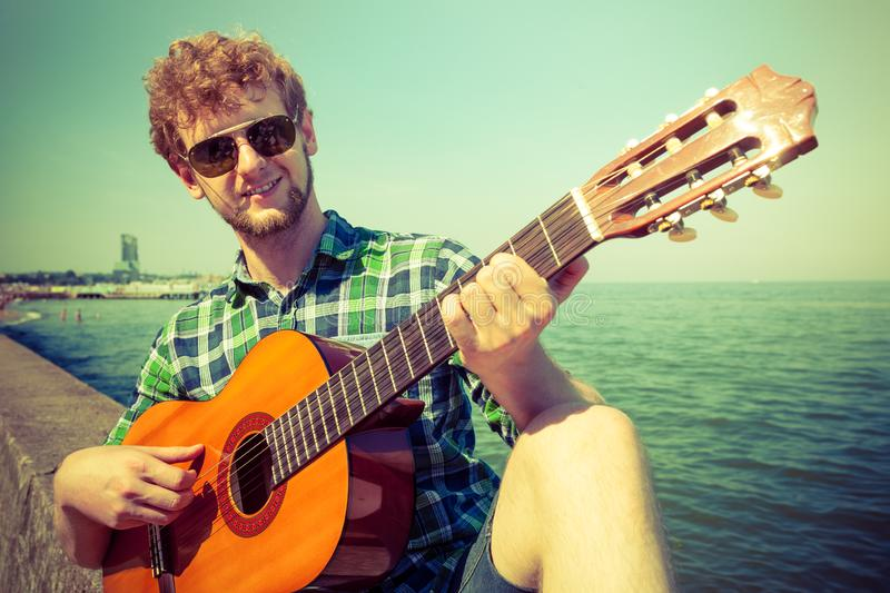 Young man hipster playing guitar by sea ocean stock photo
