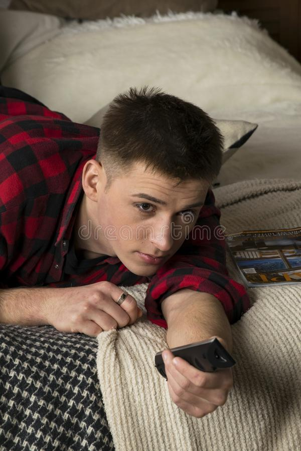 A young man in a hipster shirt lies on a bed royalty free stock photography