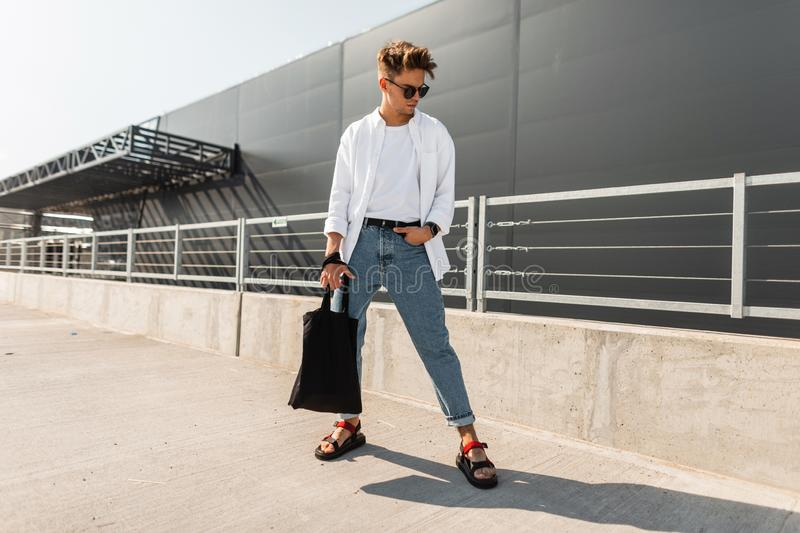 Young man hipster in stylish clothes in sunglasses with a black cloth bag in vintage sandals stands is in a city royalty free stock photography