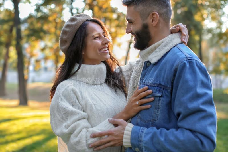 Young man with his beloved wearing engagement ring in autumn park. Young men with his beloved wearing engagement ring in autumn park stock photos