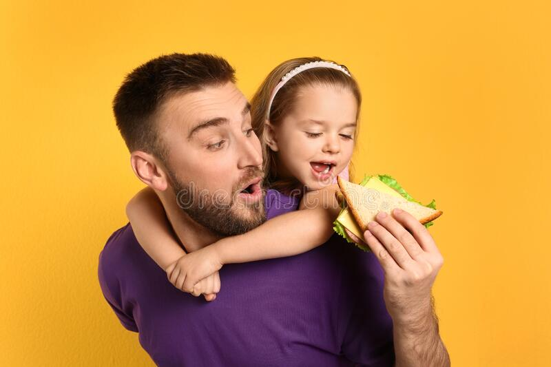 Young man and his daughter with sandwich on background stock photography