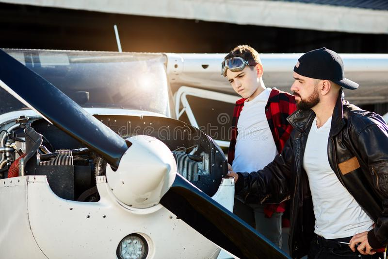 Young man with his kid brother looking puzzled at single-engine small jet royalty free stock photo