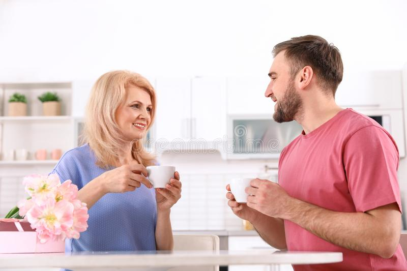 Young man and his mature mom having breakfast in kitchen stock photography