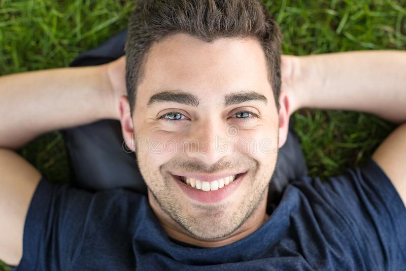 Beautiful young man with bright blue eyes lays in grass and looks up at the camera with a smile royalty free stock photos