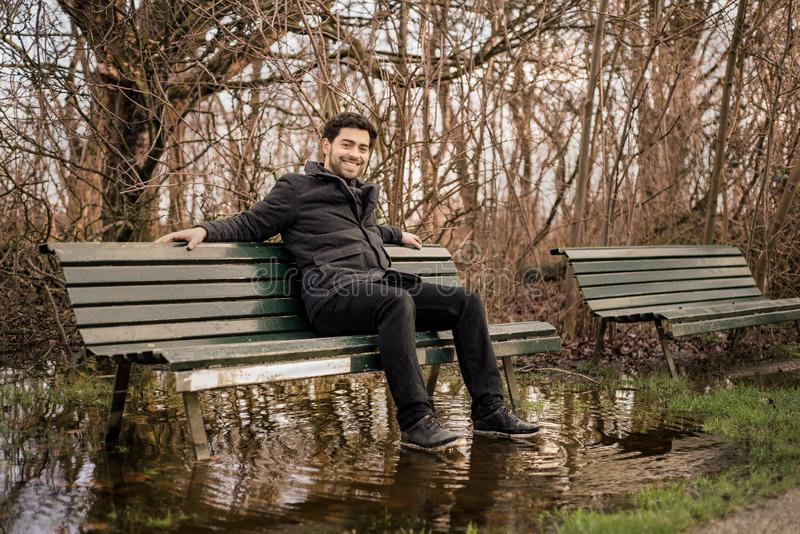 Handsome young man looking at camera while sitting on a flooded park bench in winter royalty free stock photo