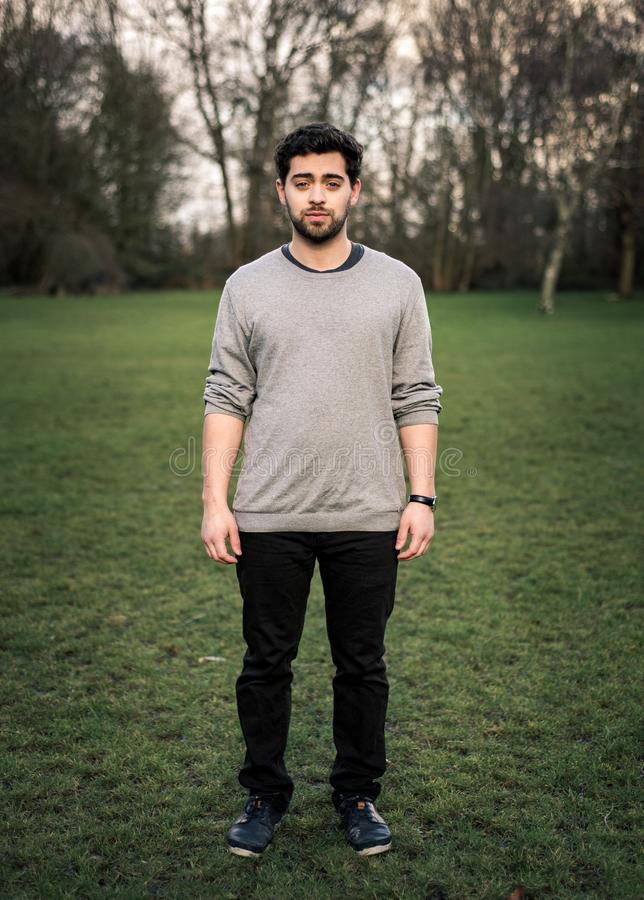Vertical full body photo of a young man standing isolated in a park, looking at the camera stock photo