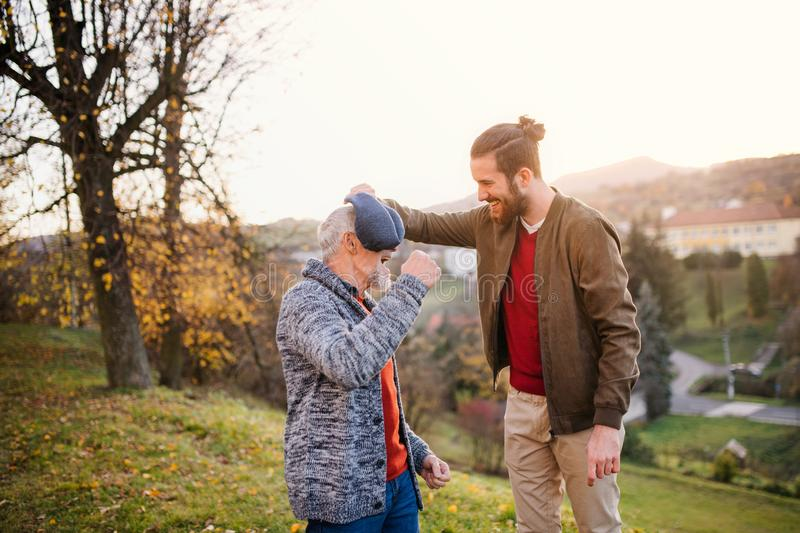 Young man and his senior father in nature, having fun. royalty free stock photography