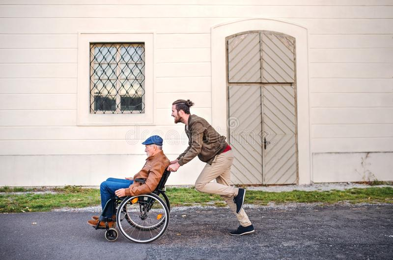 Young man and his senior father in wheelchair on a walk in town, having fun. stock images