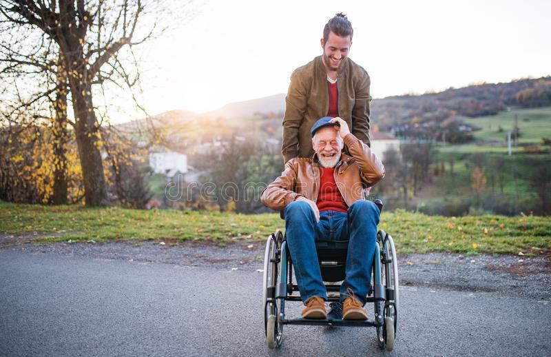 Young man and his senior father in wheelchair on a walk in town. A young men and his senior father in wheelchair on a walk in town at sunset royalty free stock images
