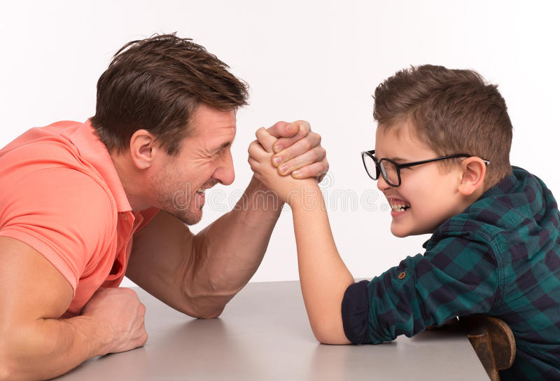 Young man and his son arm wrestling. Little boy and his dad are competing in physical strength. People sitting at the table and arm wrestling royalty free stock photography