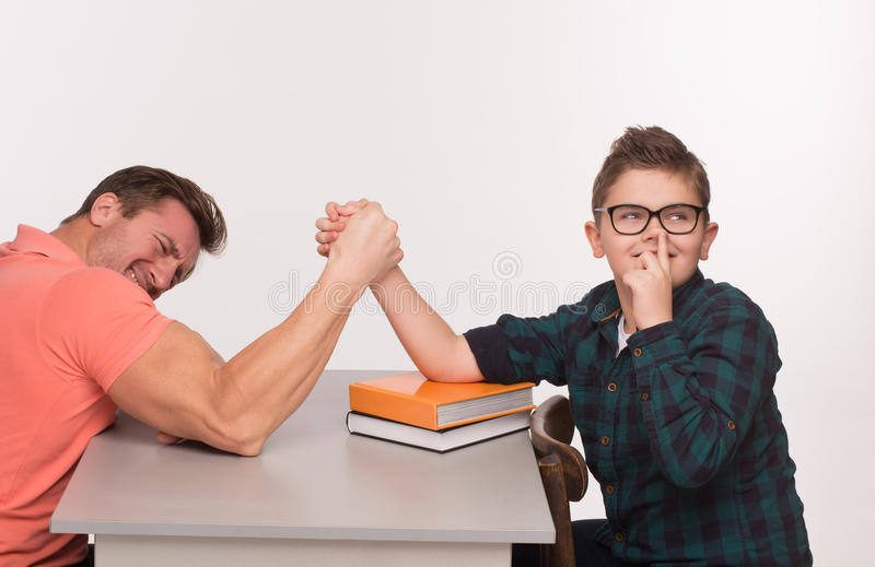 Young man and his son arm wrestling. Young men and his son having arm wrestling on while. Boy adjusting his glasses without any emotions royalty free stock photo