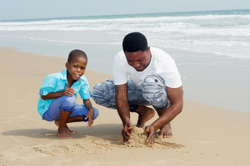 Young man and his son at the beach royalty free stock photography