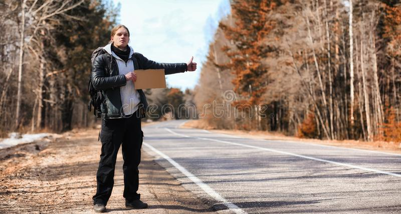 A young man is hitchhiking around the country. The man is trying. To catch a passing car for traveling. The man with the backpack went hitchhiking to south.r stock photos