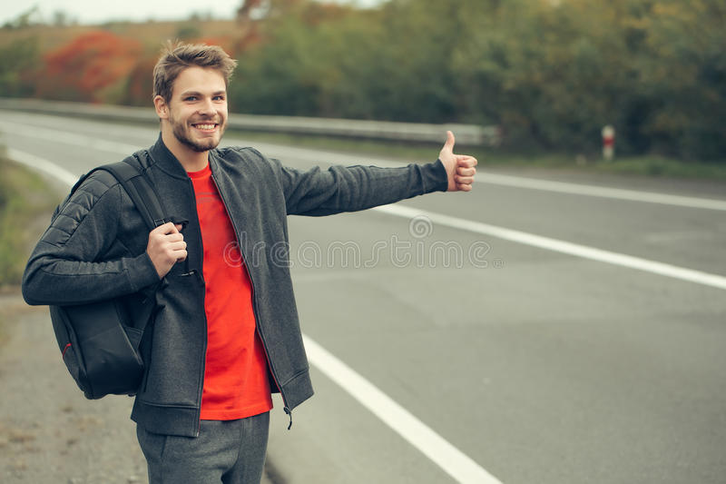 Young man hitchhiking. With bearded smiling handsome face in black and red casual clothes with bag standing near road way with hand autostop outdoor royalty free stock photo