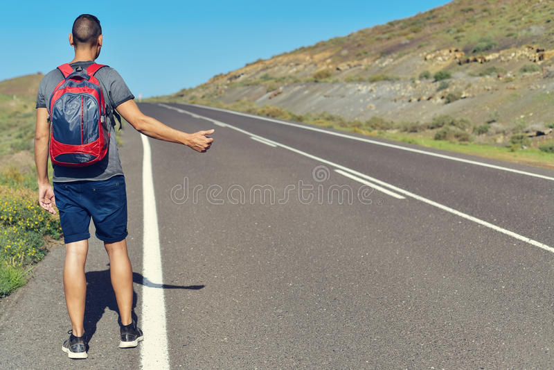 Young man hitchhiking stock photos