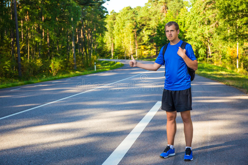 Young man hitchhiking on forest road. Young handsome man hitchhiking on forest road stock photography