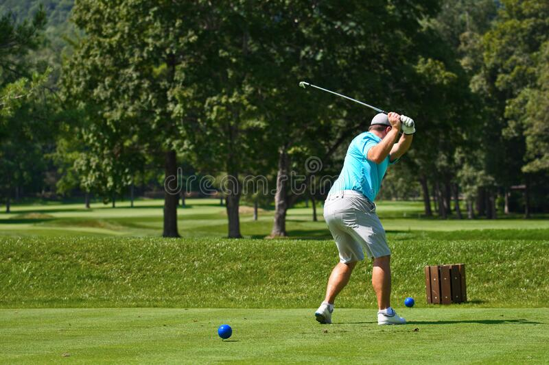 Young Man Hitting an Iron off the Tee Box royalty free stock images