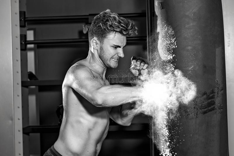 Young man hitting punching bag. A young man in the gym punches a bag hard as chalk explodes from the impact stock photo