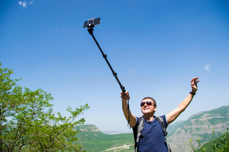 Young man hold monopod hand, taking selfie on mobile phone. Photo of the Young man hold monopod in hand taking selfie on mobile phone stock images