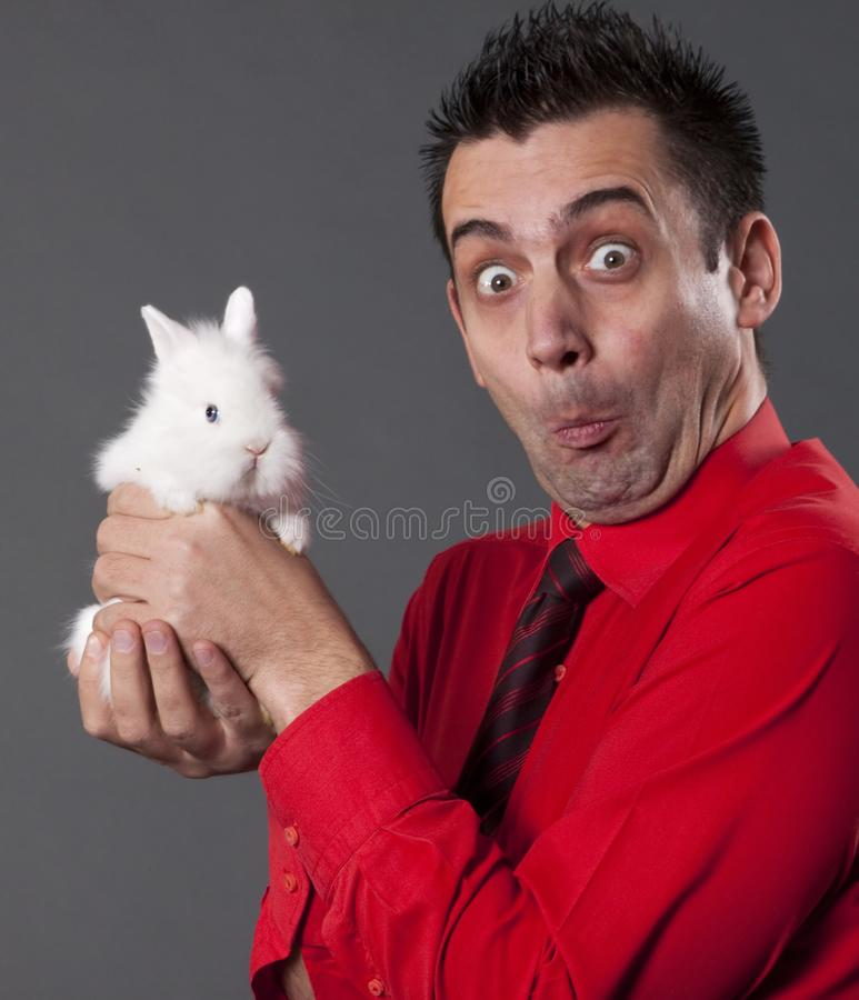Young man holding baby rabbit stock images