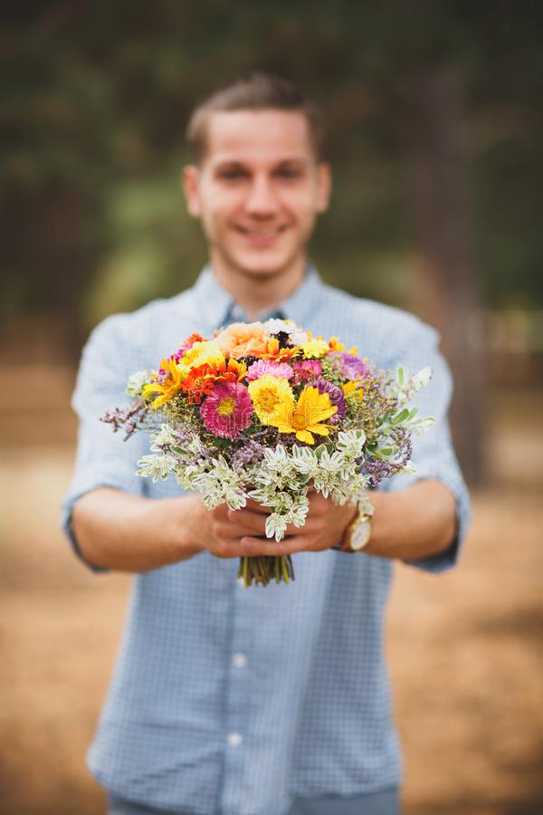 Young man holding flowers in blue shirt and shorts. Coniferous forest on a background. Beautiful autumn flowers. royalty free stock image