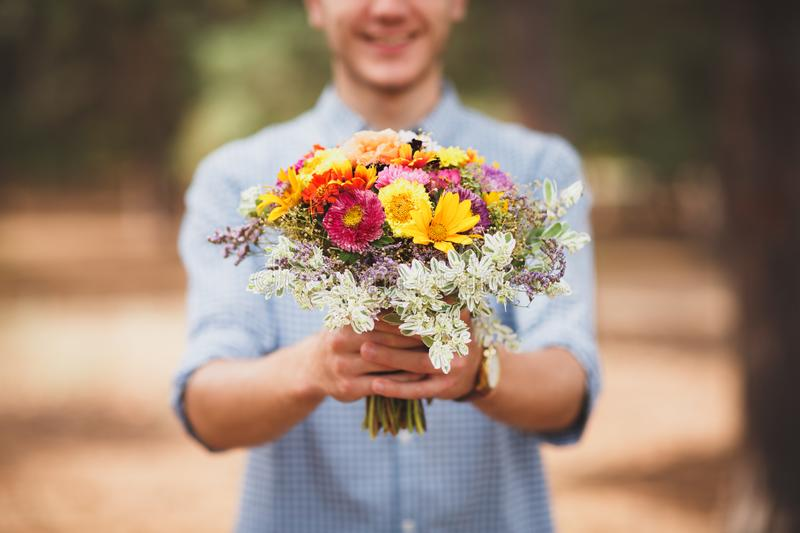 Young man holding flowers in blue shirt and shorts. Coniferous forest on a background. Beautiful autumn flowers. royalty free stock photos