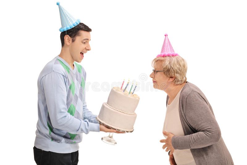 Young man holding a birthday cake with a mature woman blowing th. Young men holding a birthday cake with a mature women blowing the candles isolated on white royalty free stock photography