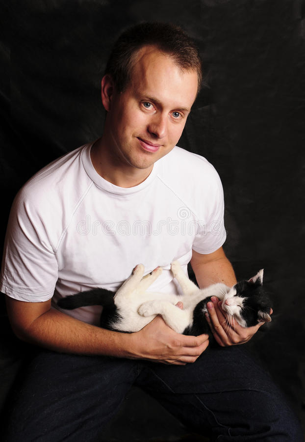 Young Man Holding A Black And White Cat Stock Photography