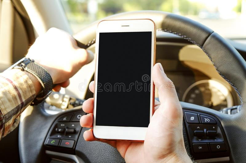Car interior with male driver sitting behind the wheel, soft sunset light. Luxurious vehicle dashboard and electronics. Young man holding blank screen cell stock images