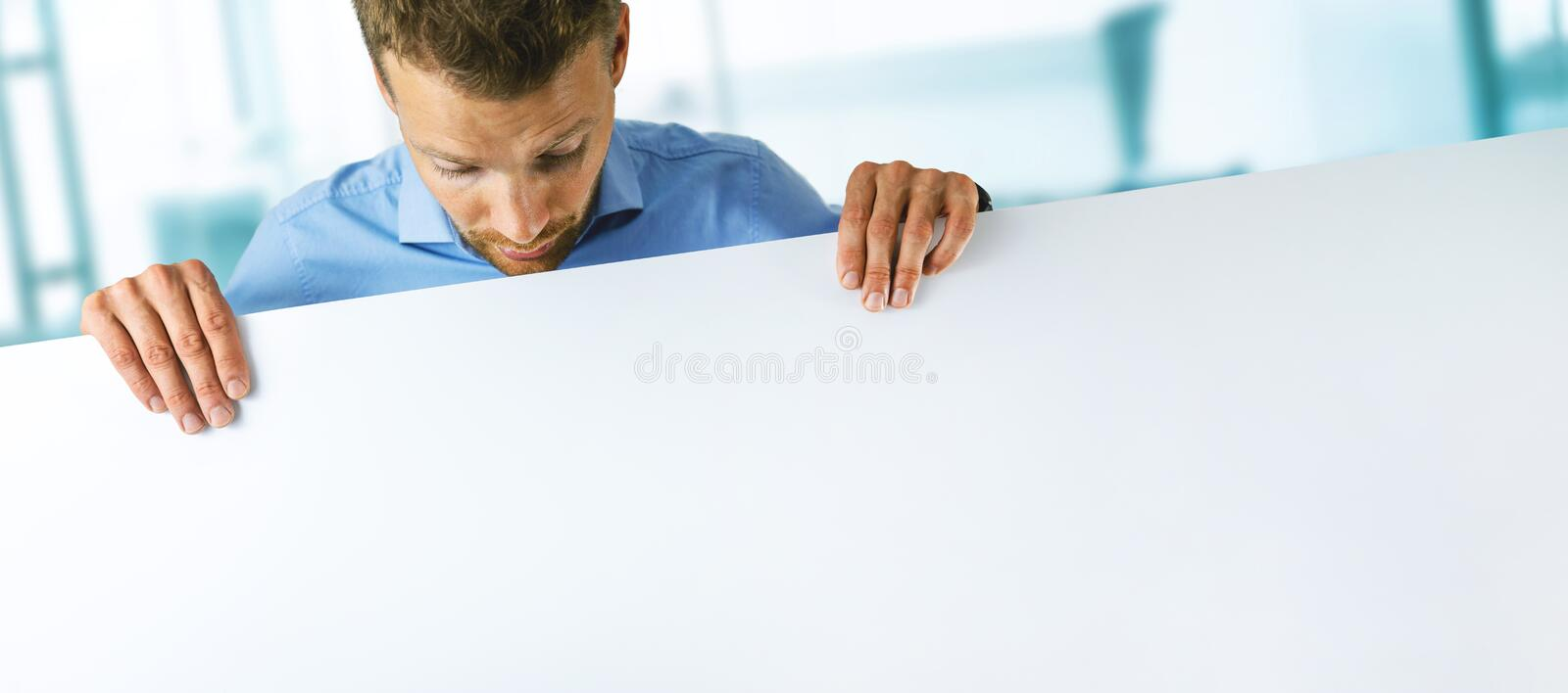 Young man holding blank white banner with copy space royalty free stock photo