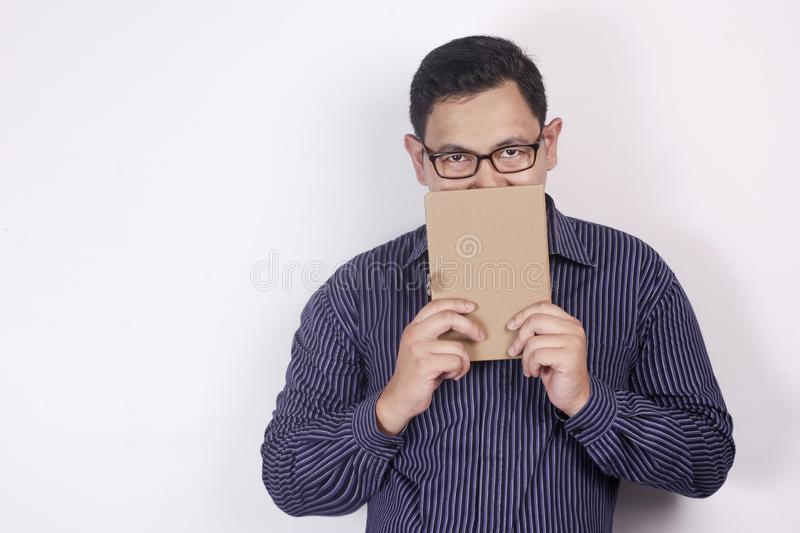 Young Man Holding Book, Mouth Covered by Book. Young Asian man covering his mouth with a book, smiled. Close up portrait against white background, indonesian royalty free stock photos