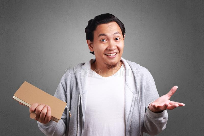 Young Man Holding Book, shrugging Gesture. Young Asian man wearing white shirt and gray jacket holding a book shrugging, smiling expression. Background on gray royalty free stock image