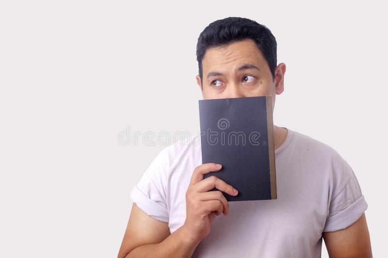Young Man Holding Book, Thinking Expression stock images