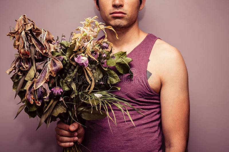 Young man holding bouquet of dead flowers. A sad young man is holding abouquet of dead and withered flowers royalty free stock images