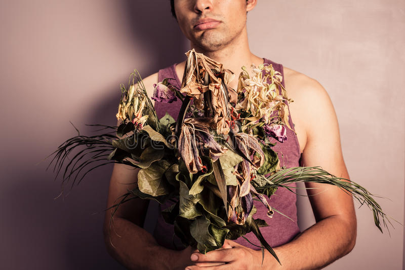 Young man holding bouquet of dead flowers. A sad young man is holding abouquet of dead and withered flowers royalty free stock image