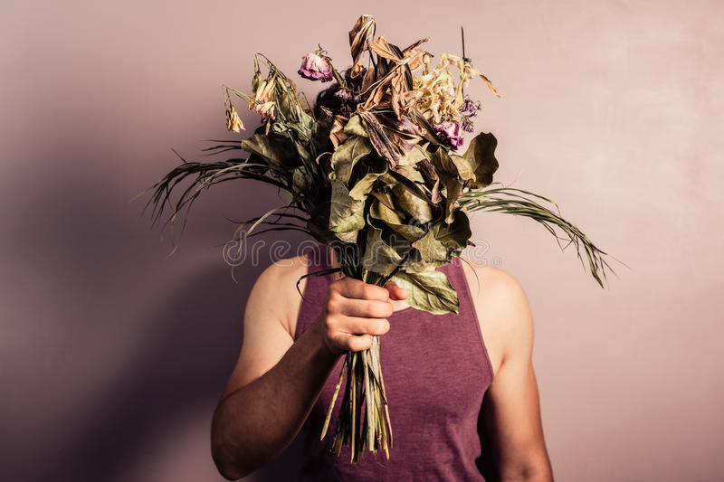 Young man holding bouquet of dead flowers. A sad young man is holding abouquet of dead and withered flowers stock photography
