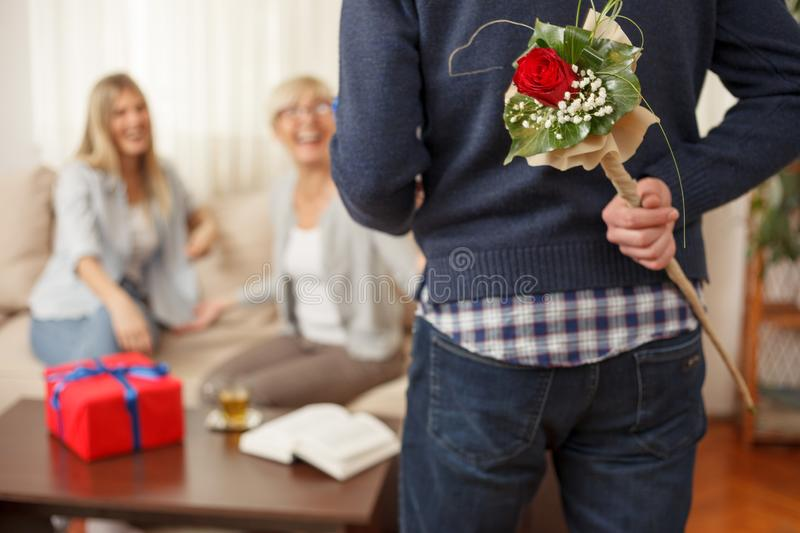 Young man holding bouquet of flowers behind the back for his mother stock photos