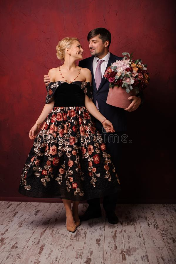 Young man holding a bouquet of flowers hugging his beautiful woman royalty free stock photos