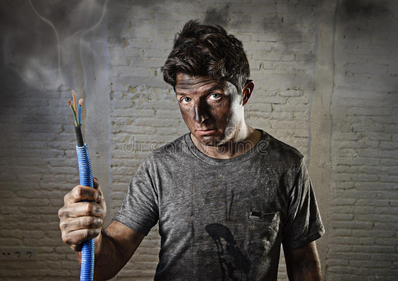 Young man holding cable smoking after electrical accident with dirty burnt face in funny sad expression. Young man holding electrical cable smoking after stock images