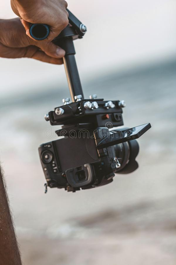Young man holding camera attached to a steadicam on background of sea, a videographer shooting video walking on the beach, a stock photo