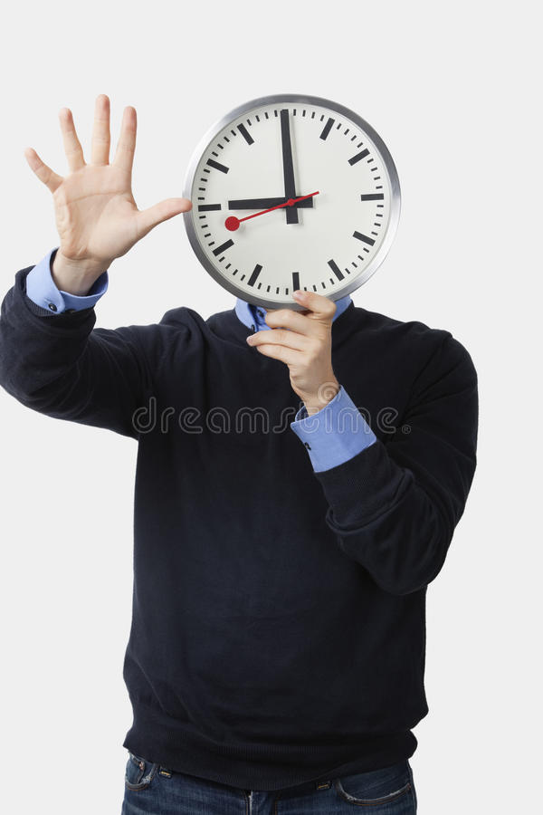 Download Young Man Holding Clock Over His Face Gesturing Against White Background Stock Image - Image: 30855437
