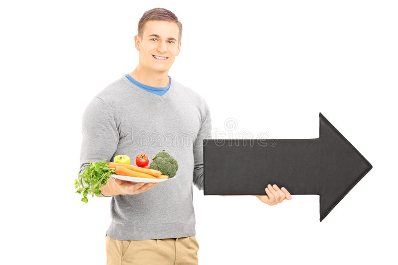 Young man holding a dish with vegetables and big black arrow poi. Nting right isolated on white background stock photos
