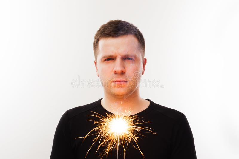 Young man holding the dying sparkler. End holidays. Distrust of pyrotechnics royalty free stock photo