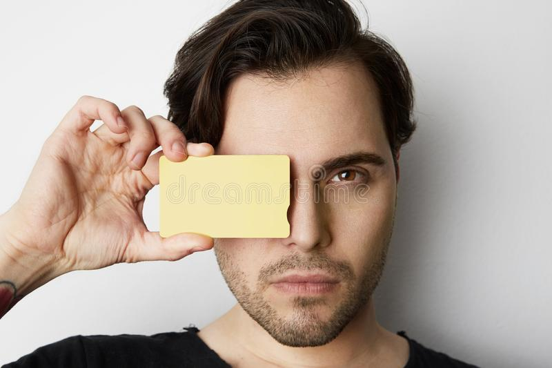 Young man holding empty yellow color credit card front of male face on blank white background. Business mock-up. Background for message writing. Horizontal stock photography