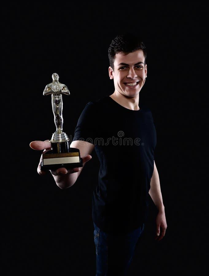 Young man holding fake oscar award. Photo of a young man holding fake oscar award with a text space. Studio photography stock photos
